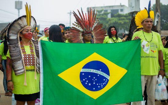 Indígenas levam bandeira do Brasil no caminho ao Coliseu Madre de Dios, onde participaram de encontro com o Papa. Foto: Tiago Miotto/Cimi